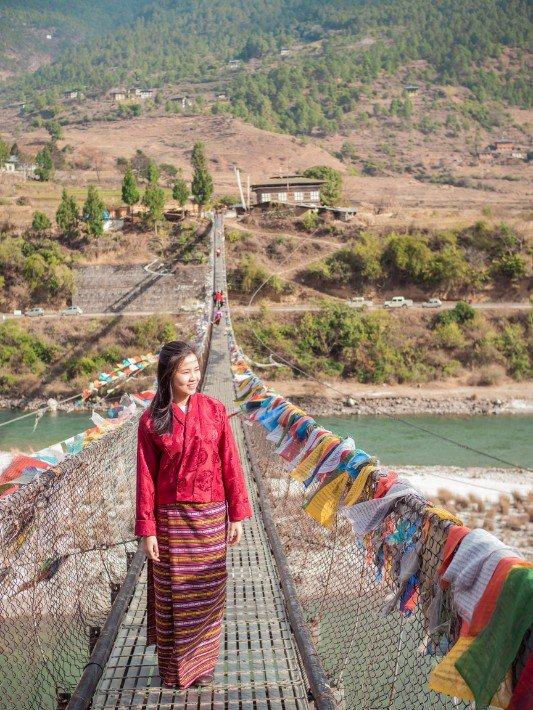 girl-in-traditional-costume-bridge-punakha-bhutan